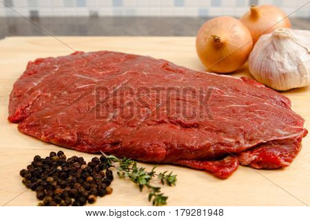 Flat iron steak A raw flat iron steak with onions garlic and herbs
