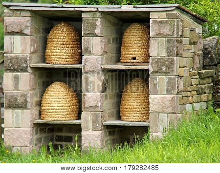 Four Wicker Beehives in a Stone Built Garden Shelter.