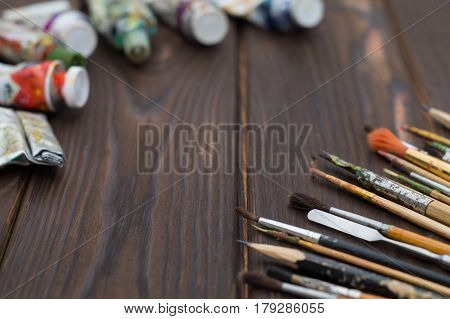 Brushes and paints are spread out on dark wooden surface