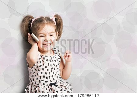 Hppy Little smiling girl talking on phone. Blue speech bubble at the top of the photo for your text