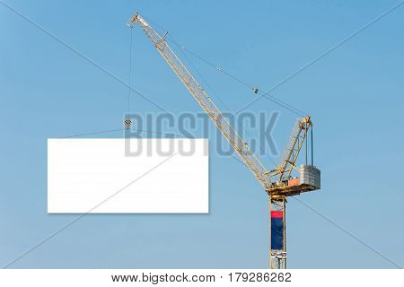 Construction crane holding a blank billboard with blue sky background. Elegant Design with copy-space on billboard for your Text