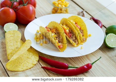 Baked taco shells with chicken mince tomato and corn and served on a white plate. Ingredients for cooking of traditional mexican tacos