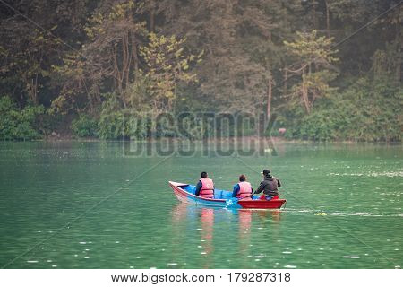 POKHARA NEPAL - DEC 19: Unidentified tourists in colourful wooden boat at Fewa lake on December 19 2015 in Pokhara Nepal. Pokhara is the major tourism Hub known for trekking and boating