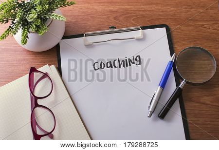 Coaching word on paper with glass ballpen and green plant .