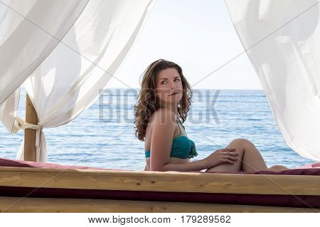 Beautiful Woman Sitting On Cozy White Lounger On The Beach. Soft Focus