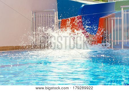 A young man is rolling on a watery crust. Spray from the diver into the pool