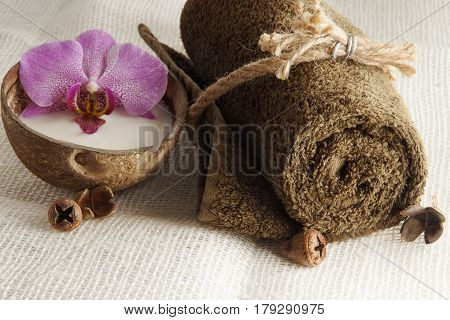 A folded towel tied with a rope and an orchid flower in milk in a coconut on a light woven napkin preparation for the spa procedure