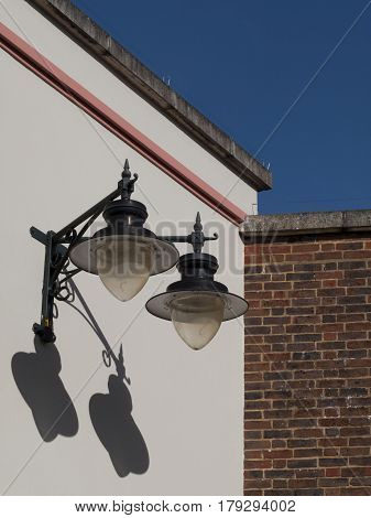Vintage style street lamps fixed to side of building
