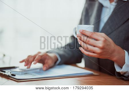 Businesswoman using calculator to analyze graph and drink coffee