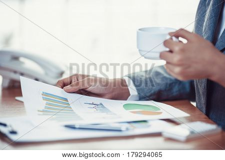 Business person reading financial graph and drink coffee