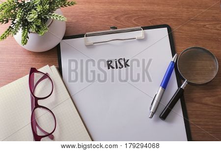 Risk Word On Paper With Glass Ballpen And Green Plant.