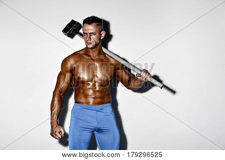 athlete and hammer. guy with a nice muscle fitness, bodybuilder hold big metal hammer