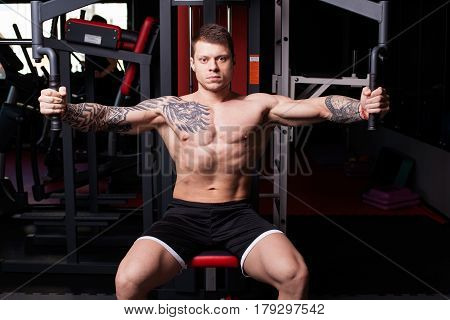 Athletic man with naked torso performing crossover exercise for chest muscles at the gym