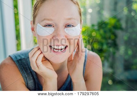 Portrait Of Beauty Red-haired Woman With Eye Patches Showing An Effect Of Perfect Skin. Spa Girl