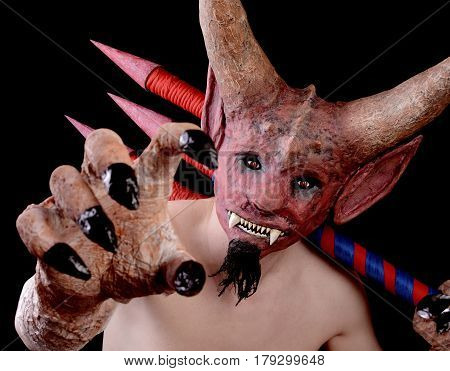 Man in the mask of the devil is threatening with his hand. Isolated on a black background