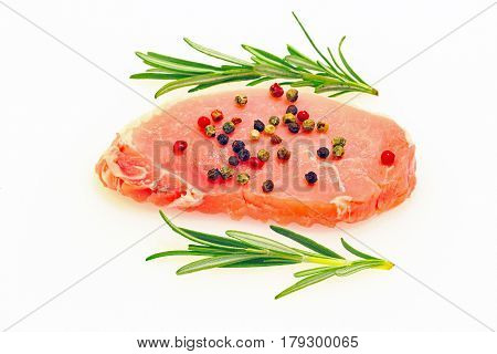 Raw cutlet of pork on a white plastic kitchen board
