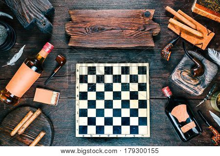 Frame of smoking pipes, cigars, tobacco and brandy bottles on dark wood desk. Chess board in the middle. Western style. Wooden signboard as title. Top view