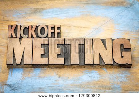 Kickoff meeting word abstract in letterpress wood type printing blocks against grunge wooden surface