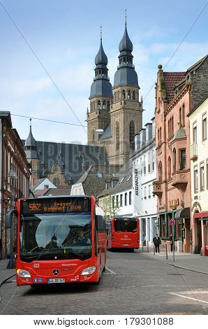 Speyer, Germany - April 11, 2015: Red city bus on background of Speyer Church. Rheinland-Pfalz.