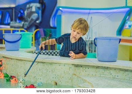 Cute boy in the playroom fishing. The development of fine motor concept. Creativity Game concept.