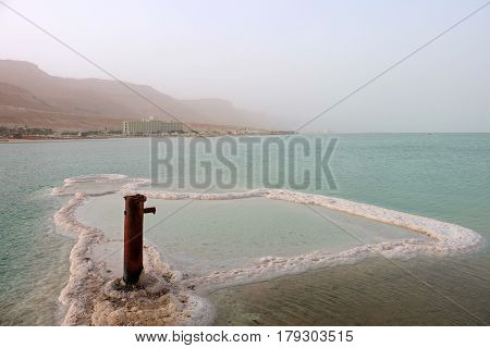 Iron pole and salt sediment on Dead Sea surface Israel
