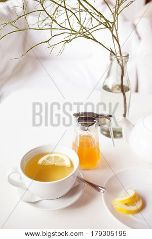 Cup of hot green tea with lemon on white table, fresh lemon and honey - closeup shot. Sun light flair effect. Nice interior in wooden house. Relaxation concept