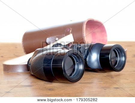 Vintage english military Porro prism black color binoculars and opened brown hard leather carry case on wooden background indoor over white side view closeup