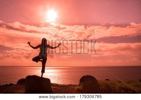 a woman silhouetted practicing yoga along the Maui coast