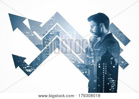 Side portrait of thoughtful young man with arrows on city background. Finance concept. Double exposure