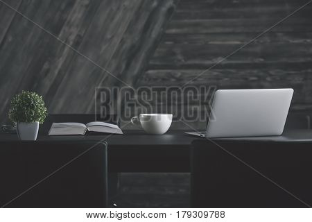 Front view of stylish office desk with plant open book coffee cup and laptop. Dark wooden wall in the background. Creative designer desktop