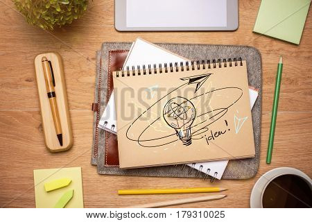 Top view of wooden desktop with creative light bulb sketch inn notepad coffee cup supplies and other items. Idea concept