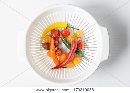 Chili pepper green, red, yellow, orange, cherry tomatoes in a bowl sieve against white background