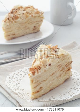 Mille feuille dessert. Piece of multi layered cake close-up. Crumbs decorated torte on white doily upon wooden table. Food background, blur. Selective focus on the front.