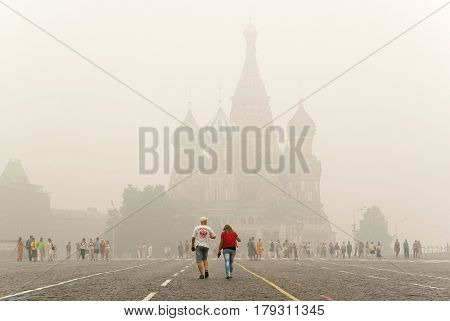 MOSCOW - AUGUST 7, 2010: Unidentified tourists go to Intercession Cathedral on the Red Square under smog in Moscow. City covered an unprecedented smoke from burning forests.