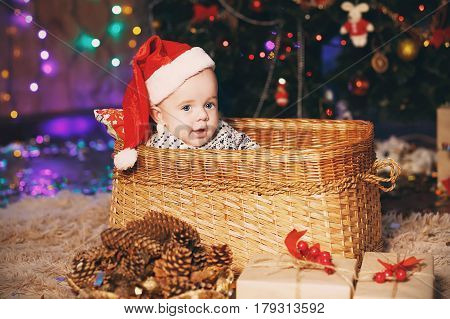 Little Baby Boy in Santa hat sitting in a wicker basket. New Year and Christmas concept