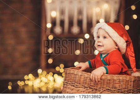 Little Baby Boy In Santa Hat Sitting In A Wicker Basket