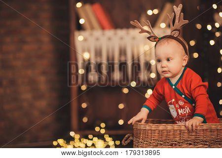 Little Baby Boy In Reindeer Antlers Sitting In A Wicker Basket.