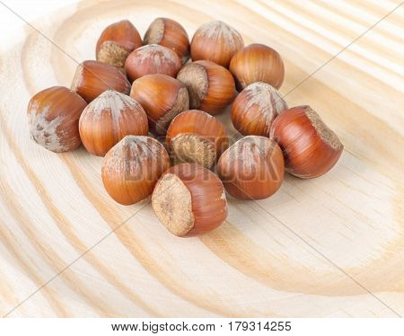 Pile of hazelnuts in nutshells on the wooden background