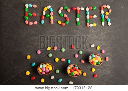 Easter written with colorful candies on chalkboard background with chocolate eggs.