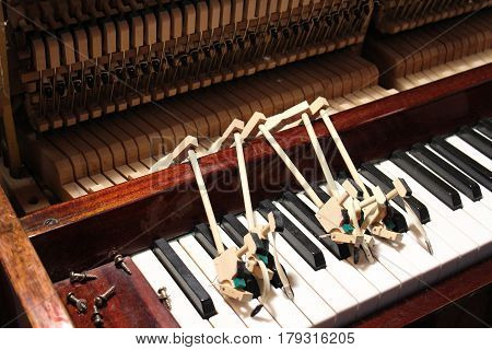 The tuner man is mending and tuning the old piano