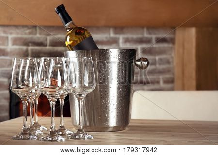 Wine bottle in bucket with ice and glasses on table
