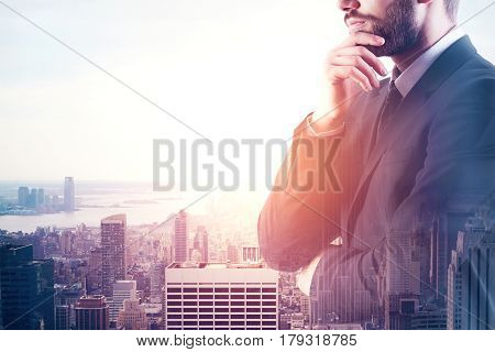 Side view of young euyropean businessman on city background. Research concept. Double exposure