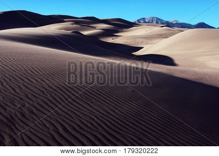 Afternoon shadows creep across the windswept sands of the Great Sand Dunes National park near Alamosa, Colorado