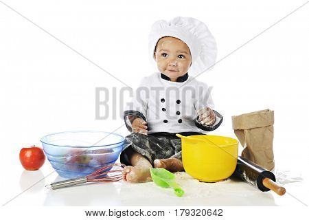 An adorable baby boy playing chef in a chef's outfit, backing equipment, apples and flour. On a white background.