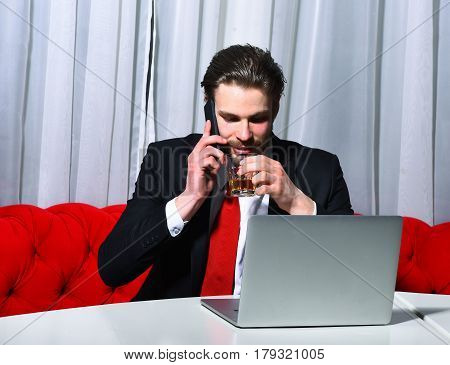 bearded man businessman long beard brutal caucasian hipster with moustache holding glass with whiskey has happy face unshaven guy with stylish hair in suit and red tie works at laptop computer