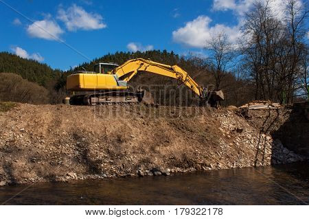 Excavator on the work to strengthen the shoreline of the river