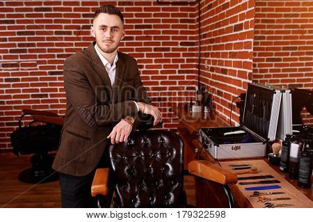 Portrait of the hairdresser. Cheerful young bearded man looking at camera and leaning on chair at barbershop. Armchair and instruments for barbershop. Professional and craftmanship. Hairdresser in the brown jacket. Background of brick wall.