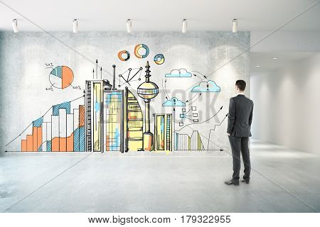 Thoughtful businessman in concrete room looking at wall with creative city sketch with business charts. Industry concept