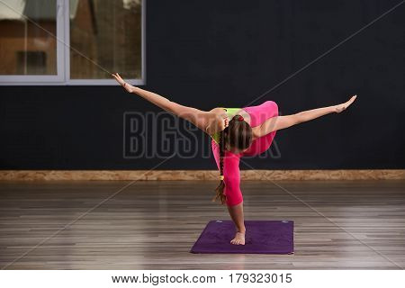 Beautiful young Woman Standing On One Leg And Exercising Over dark Background. Doing yoga exercises in the gym on the violet yoga mat. WOman in the sportwear, green t-shirt and pink leggings. Healthy lifestyle.