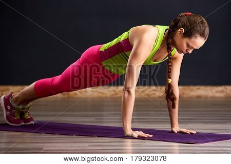 Young attractive woman practicing yoga, doing Push ups or press ups on the violet mat. Working out, wearing green t-shirt and pink leggings. Yoga studio. Healthy lifestyle.